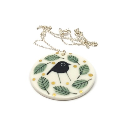 Porcelain pendant - Black bird in green leaves with gold lustre